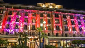 Façade illuminée en rouge de l'hôtel Le Royal à Nice