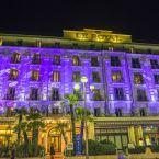 Façade illuminée en violet de l'hôtel Le Royal à Nice